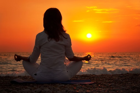 woman-meditating-on-beach-at-sunse_450